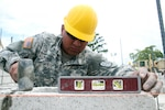 Pfc. Alfredo Ponce, a carpenter with the 808th Engineer Company, levels a cinder block on the foundation of a new medical clinic April 15, 2017, during a construction project at Double Head Cabbage, Belize as part of Beyond the Horizon 2017.  The construction project is one of five scheduled for Beyond the Horizon 2017, a U.S. Southern Command-sponsored, Army South-led exercise designed to provide humanitarian and engineering services to local communities in Belize. (U.S. Army Photo by Staff Sgt. Fredrick Varney, 131st Mobile Public Affairs Detachment)