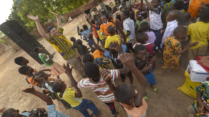 Air Force Col. Ric Trimillos dances with children during a performance by Touch 'n Go, the U.S. Air Forces in Europe popular music ensemble, in Ouagadougou, Burkina Faso, April 19, 2017. Air Force photo by Staff Sgt. Jonathan Snyder