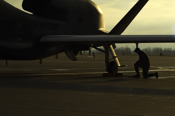 An Airman with the 69th Maintenance Squadron kneels beneath the wing of an RQ-4 Global Hawk March 25, 2017, on Grand Forks Air Force Base, N.D. Airmen with the 69th MXS performed the first Air Force-led Mobile Automated Scanner scan on this aircraft, which allowed it to continue its part in supporting the combatant commands. (U.S. Air Force photo by Senior Airman Ryan Sparks)