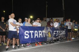 Personnel throughout the U.S. Army Central area of operations hold the Boston Athletic Association 'Start Finish' banner before the start of the Boston Marathon Shadow Run, April 17, Camp Arifjan, Kuwait. This race shadowed the 121st Boston Marathon, but was the first for Camp Arifjan, and gave deployed personnel an opportunity to participate in the famous marathon. (U.S. Army photo by Sgt. Kimberly Browne, USARCENT Public Affairs)
