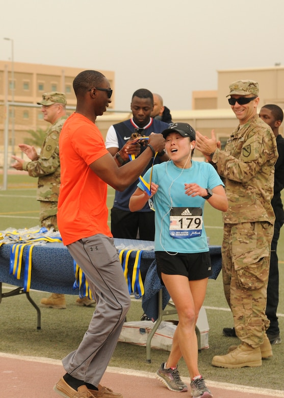 Maj. Jeannie Huh, a Soldier with the 31st Combat Support Hospital, receives her Boston Marathon Shadow Run participation medal after placing first in the women's division with a time of three hours, 15 minutes, 33 seconds, in Camp Arifjan's first Boston Marathon Shadow Run, April 17, Camp Arifjan, Kuwait. This race shadowed the 121st Boston Marathon, and gave deployed personnel an opportunity to run in the well-known marathon. More than 300 people participated in the shadow run.  (U.S. Army photo by Sgt. Kimberly Browne, USARCENT Public Affairs)