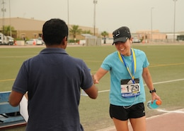 Maj. Jeannie Huh, a Soldier with the 31st Combat Support Hospital, a bottle of water from a volunteer after placing first in the women's division with a time of three hours, 15 minutes, 33 seconds, in Camp Arifjan's first Boston Marathon Shadow Run, April 17, Camp Arifjan, Kuwait. This race shadowed the 121st Boston Marathon, and gave deployed personnel an opportunity to run in the famous marathon. More than 300 people participated in the shadow run.  (U.S. Army photo by Sgt. Kimberly Browne, USARCENT Public Affairs)