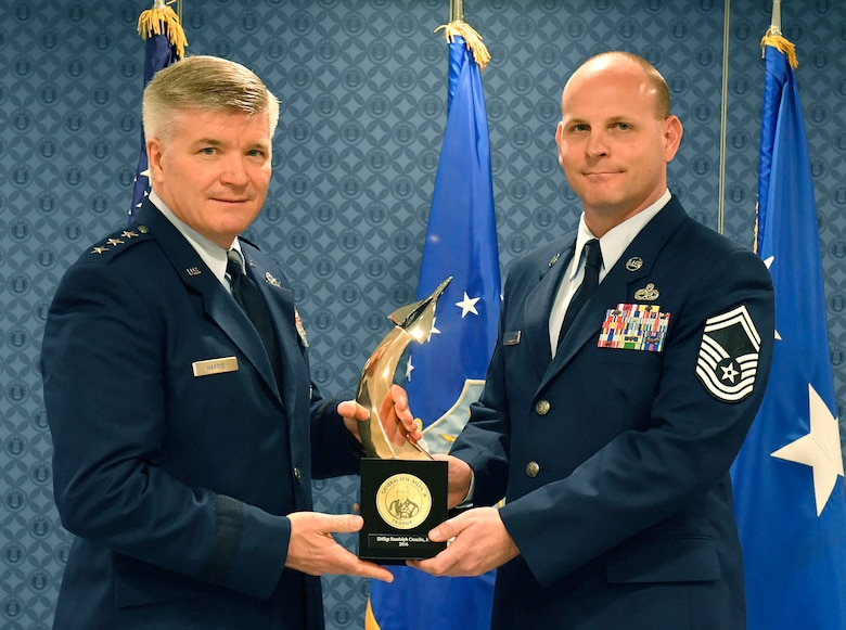 Lt. Gen. Jerry Harris, the deputy chief of staff for strategic plans, programs and requirements, presents Senior Master Sgt. Randolph Crosslin Jr. the Gen. Lew Allen Jr. Trophy for 2016, during a ceremony at the Pentagon, April 21, 2017. (U.S. Air Force photo/Wayne A. Clark)