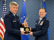 Lt. Gen. Jerry Harris, the deputy chief of staff for strategic plans, programs and requirements, presents Maj. Jessica Stewart the Gen. Lew Allen Jr. Trophy for 2016 during a ceremony at the Pentagon, April 21, 2017. (U.S. Air Force photo/Wayne A. Clark)