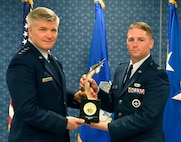 Lt. Gen. Jerry Harris, the deputy chief of staff for strategic plans, programs and requirements, presents Capt. Joseph Spada the Gen. Lew Allen Jr. Trophy for 2016 during a ceremony at the Pentagon, April 21, 2017. (U.S. Air Force photo/Wayne A. Clark)