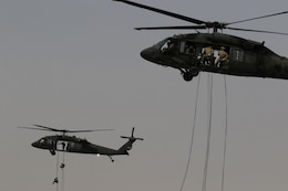 U.S. Servicemembers rappelling out of UH-60 Black Hawk helicopters during day nine of U.S. Army Central's first Air Assault Course, April 13, 2017 at Camp Beuhring, Kuwait. The Air Assault Course is a 12-day class that allows U.S. military personnel in the USARCENT area of operations the unique opportunity to become air assault qualified, while deployed outside the continental United States.