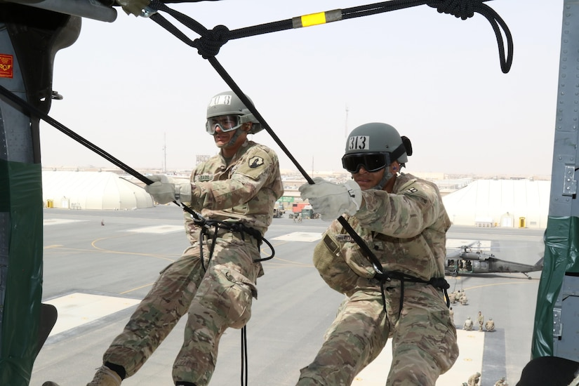 U.S. Army Spc. Melendez Casado (left), horizontal construction engineer, 176th Engineer Brigade, and Army Spc. Elijah Gould (right), pharmacy specialist, 3rd Medical Command Deployment Support, prepare to rappel out of a UH-60 Black Hawk helicopter during U.S. Army Central's first Air Assault Course, April 13, 2017, at Camp Beuhring, Kuwait. The Air Assault Course is a 12-day class that allows U.S. military personnel in the U.S. Army Central area of operations the unique opportunity to become air assault qualified, while deployed outside the continental United States.