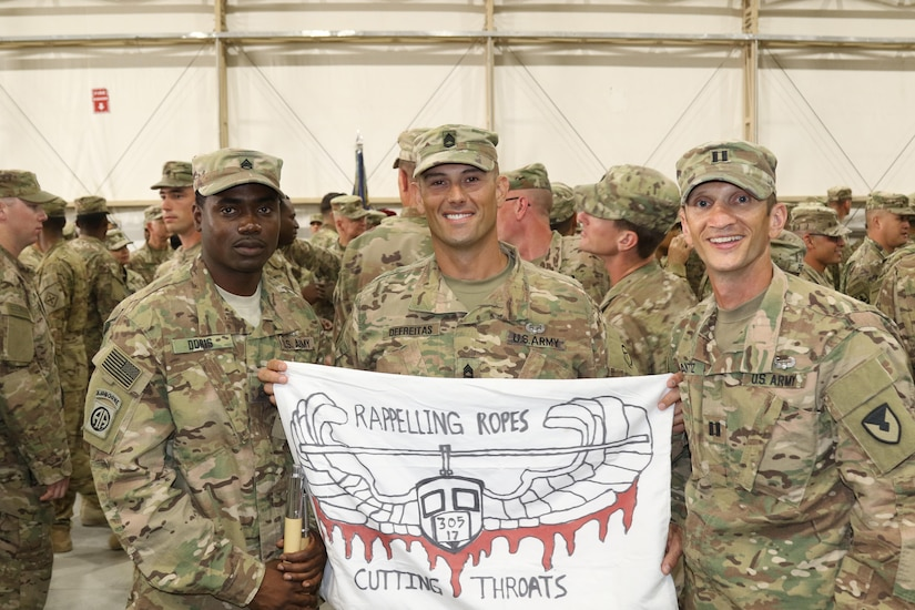 U.S. Army Staff Sgt. Doris (left), acquisitions, logistics and technology non-commissioned officer, 408th Contracting Support Brigade; Sgt. 1st Class Renato Defreitas (center), instructor, Basic Leaders Course, and Capt. Frank Antosz, infantry officer, 408th Contracting Support Brigade, hold up the guide-on during graduation day of U.S. Army Central's first Air Assault Course, April 14, 2017, at Camp Beuhring, Kuwait. The Air Assault Course is a 12-day class that allows U.S. military personnel in the U.S. Army Central area of operations the unique opportunity to become air assault qualified, while deployed outside the continental United States.