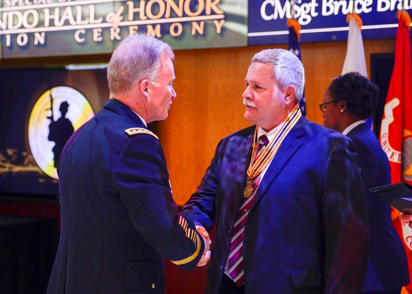 Army Gen. Raymond A. Thomas, USSOCOM commander, and Command Sgt. Maj. Patrick L. McCauley, USSOCOM command senior enlisted adviser recognizes Chief Master Sgt. Bruce Brandewie during the 2017 Commando Hall of Honor Ceremony located at the USSOCOM headquarters, MacDill Air Force Base, Florida, April 18.  CMSgt  Brandewie embody the skills, values, spirit and courage of a Special Operations Forces Warrior and was one of the seven inductees that were honored during this ceremony.