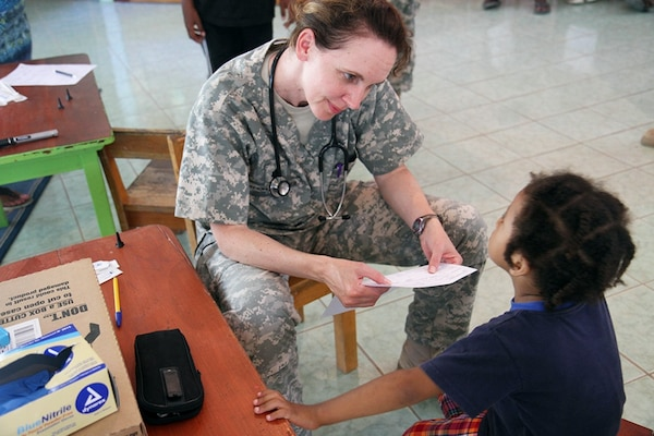Lt. Col. Erin Merryweather, deputy commander of clinical services, Utah Medical Command, evaluates a young patient in Ladyville, Belize, April 18, 2017, during a community relations event held as part of Beyond the Horizon 2017. Army Photo by Staff Sgt. Fredrick Varney