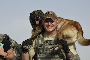 U.S. Air Force Staff Sgt. Christopher Kench, a military working dog handler with the 379th Expeditionary Security Forces Squadron, carries his military working dog Beta towards the end of a three-mile ruck at Al Udeid Air Base, Qatar, April 20, 2017. The carrying of one's military working dog across the final stretch was meant to be symbolic of teamwork during the commemoration ruck march. (U.S. Air Force photo by Senior Airman Cynthia A. Innocenti)