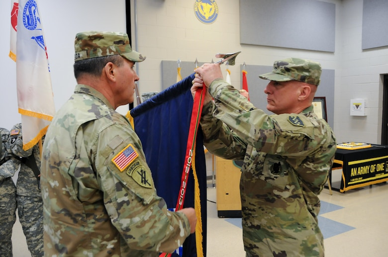 Maj. Gen. Troy D. Kok, commanding general of the U.S. Army Reserve's 99th Regional Support Command (right), and Command Sgt. Maj. Al Almeida, 99th RSC command sergeant major, affix the Army Superior Unit Award streamer to the 99th RSC Colors during a ceremony April 21 at the command's headquarters on Joint Base McGuire-Dix-Lakehurst, New Jersey. The 99th RSC received the award for providing aid and assistance from October 2012 to April 2013 to communities in New York City that were devastated by Superstorm Sandy.
