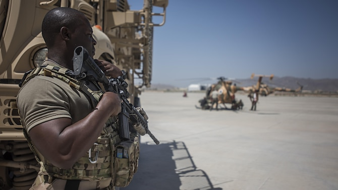 Senior Airman Micheal Thomas, 738th Air Expeditionary Advisory Group guardian angel, provides armed overwatch for contractors and air advisors performing maintenance on an Afghan Air Force MD-530 Light Attack Helicopter, April 16, 2017, at Kandahar Air Wing, Afghanistan. Thomas is deployed with other Citizen Airmen from the 507th Security Forces Squadron, Tinker Air Force Base, Okla. (U.S. Air Force photo/Staff Sgt. Katherine Spessa)