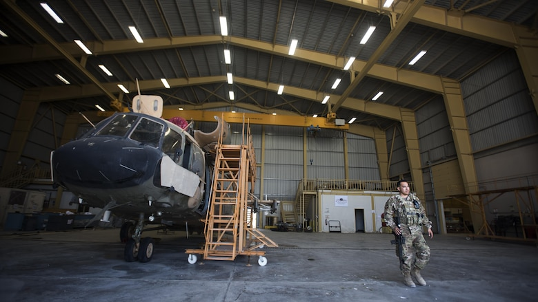 Tech. Sgt. Hector Flores, 738th Air Expeditionary Advisory Group guardian angel, provides armed overwatch for contractors and air advisors performing maintenance on an Afghan Air Force Mi-17 Military Transport Helicopter April 16, 2017, at Kandahar Air Wing, Afghanistan. Flores is deployed with other Citizen Airmen from the 507th Security Forces Squadron, Tinker Air Force Base, Okla. (U.S. Air Force photo/Staff Sgt. Katherine Spessa)