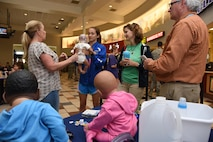 Paula Spooner, 81st Medical Operations Squadron family advocacy outreach manager, conducts a shaken baby syndrome simulation in the base exchange April 21, 2017, on Keesler Air Force Base, Miss. The family advocacy staff manned a booth with hand-outs and reading material about child abuse prevention for Keesler personnel in recognition of Child Abuse Prevention Month. (U.S. Air Force photo by Kemberly Groue)