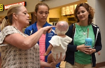 Paula Spooner, 81st Medical Operations Squadron family advocacy outreach manager, provides a shaken baby syndrome simulation to Isabelle and Lori Wheeler in the base exchange April 21, 2017, on Keesler Air Force Base, Miss. The family advocacy staff manned a booth with hand-outs and reading material about child abuse prevention for Keesler personnel in recognition of Child Abuse Prevention Month. (U.S. Air Force photo by Kemberly Groue)