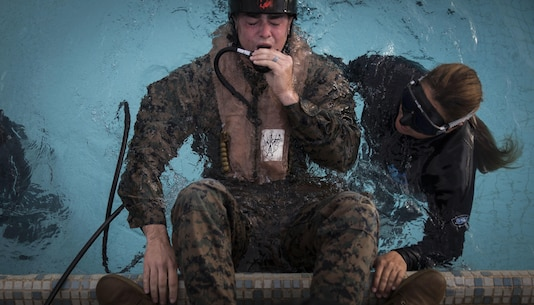 Lance Cpl. Caleb Crabtree, a rifleman assigned to Bravo Company, 1st Battalion, 3rd Marine Regiment, practices using an Emergency Breathing System during Helicopter Underwater Egress Training at the pool aboard Marine Corps Base Hawaii on March 23, 2017. The purpose of this training is to prepare service members for an emergency exit in case of a crash landing into water. (U.S. Marine Corps photo by Lance Cpl. Matthew Kirk)