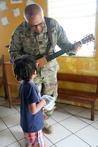 Capt. Julio Vargas, a chaplain with the 448th Engineer Battalion, plays a guitar for the children at Liberty Children's Home April 18, 2017, during a community relations event held in Ladyville, Belize as part of Beyond the Horizon 2017.  Servicemembers helped to clear debris from the property, played games and sang songs with the home's children during the event. BTH 2017 is a partnership exercise between the Government of Belize and U.S. Southern Command that will provide three free medical service events and five construction projects throughout the country of Belize from March 25 until June 17. (U.S. Army Photo by Staff Sgt. Fredrick Varney)