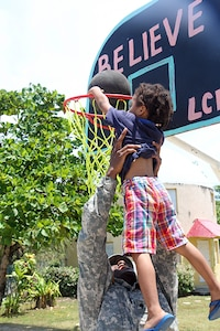 Spc. Rudy Sneed, a shower and laundry specialist with the 452nd Quartermaster Company, lifts a small child into the air at Liberty Children's Home April 18, 2017, during a community relations event held in Ladyville, Belize as part of Beyond the Horizon 2017.  BTH 2017 is a U.S. Southern Command-sponsored, Army South-led exercise designed to provide humanitarian and engineering services to communities in need, demonstrating U.S. support for Belize. (U.S. Army Photo by Staff Sgt. Fredrick Varney)