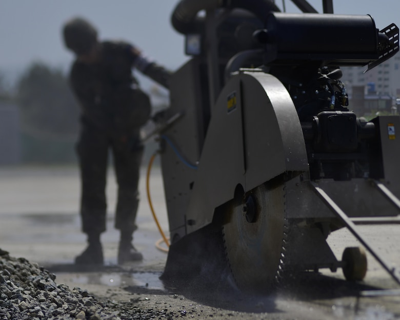 A Republic of Korea Airman cuts concrete during the U.S./ROK Combined Airfield Damage Repair Exercise at Daegu Air Base, April 19, 2017. The annual exercise ensures seamless interoperability between the U.S. and ROK while conducting airfield damage repair and improves their capability and commitment to work together at a moment's notice. (U.S. Air Force photo by Staff Sgt. Alex Fox Echols III)
