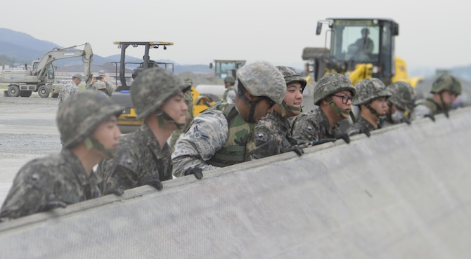 U.S. and Republic of Korea Airmen lift a rapid-runway repair fiberglass mat during the U.S./ROK Combined Airfield Damage Repair Exercise at Daegu Air Base, April 20, 2017. For five days, U.S. and ROK Airmen repaired damaged runway sections sharing techniques, strengthening bonds and forging friendships between the two allied countries. (U.S. Air Force photo by Staff Sgt. Alex Fox Echols III)