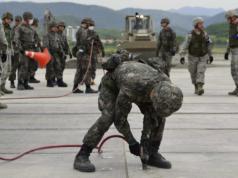 A Republic of Korea Airman secures a rapid-runway repair fiberglass mat during the U.S./ROK Combined Airfield Damage Repair Exercise at Daegu Air Base, April 20, 2017. After the mat is set up, Airmen place it over sections of damaged runway to ensure a safe launch and recovery of aircraft. (U.S. Air Force photo by Staff Sgt. Alex Fox Echols III)