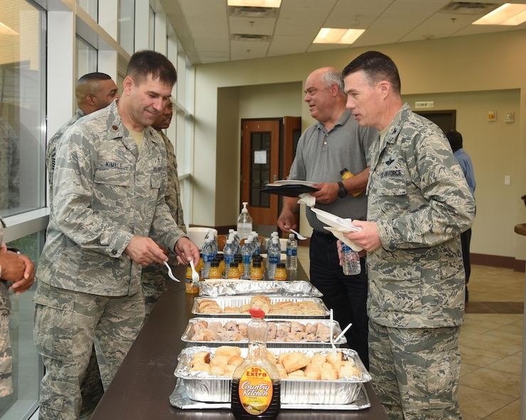Chaplain (Maj.) Bradley Kimble, Deputy Wing Chaplain, hands Col. Douglas Gosney, 14th Flying Training Wing Commander, a biscuit during a prayer breakfast April 19, 2017, at Columbus Air Force Base, Mississippi. The Chapel provides refreshments to many community events to build relationships with Airmen around the base. (U.S. Air Force photo by Melissa Doublin)