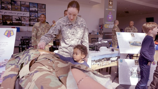 Sgt. Pattisue Graham, a member of the Medical Support Unit - Europe, explains a CPR mannequin to a child Friday, April 21 at the Kaiserslautern Military Community Center on Ramstein Air Base. Her units, part of the Army Reserve's 7th Mission Support Command, was celebrating the 109th Army Reserve birthday during the event.