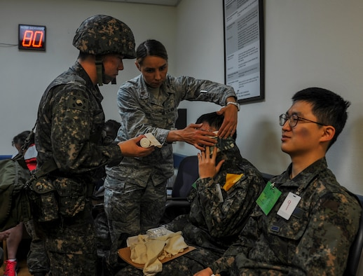 United States Air Force Maj. Anna Fedotova, 8th Medical Operation Squadron mental health flight chief, and a Republic of Korea Air Force medical airman work together to bandage a ROKAF airman's head during a mass casualty exercise at Kunsan Air Base, Republic of Korea, April 19, 2017. U.S. and ROK airmen conducted the training to evaluate their ability to communicate and operate through a MASCAL situation. (U.S. Air Force photo by Senior Airman Colville McFee/Released)