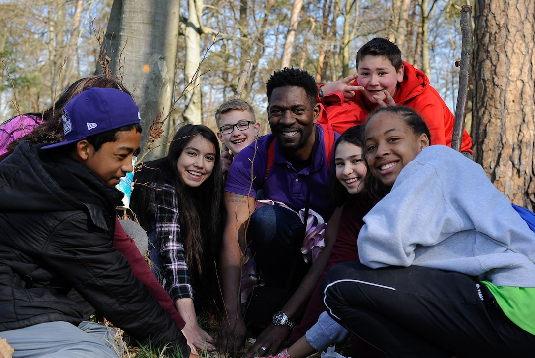 Ahmaed Cephus, Ramstein Middle School Advancement via Individual Determination (AVID) instructor, poses for a photo as he plants a tree with his students on Ramstein Air Base, Germany, April 21, 2017. Students celebrated Earth Day demonstrating support for environmental protection by planting trees. (U.S. Air Force photo by Airman 1st Class Savannah L. Waters)