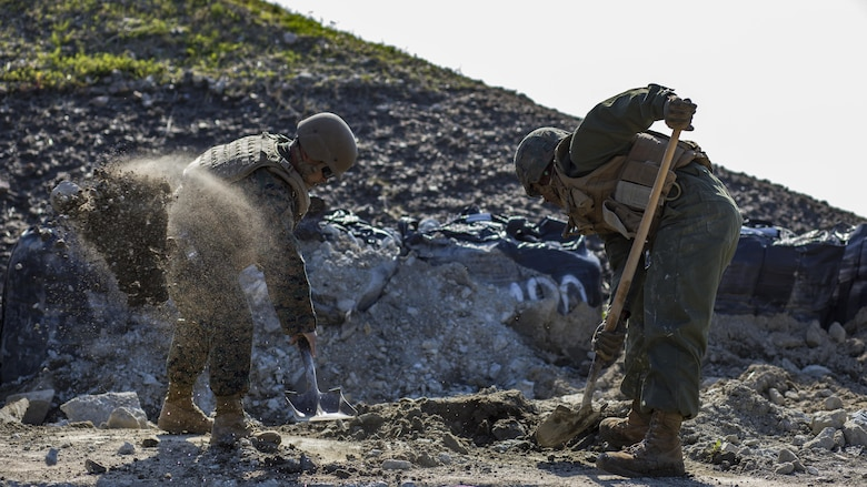 U.S. Marine Corps Gunnery Sgt. Myron Sato, left, the combat engineer staff-non-commissioned-officer-in-charge for Marine Wing Support Squadron 171, and Pfc. Jason Taylor, right a combat engineer with MWSS-171, shovel dirt and mud during airfield damage and repair training at Marine Corps Air Station Iwakuni, Japan, April 19, 2017. The ADR training required Marines to utilize their skill set to tactically and proficiently fix any anomalies to a simulated damaged airfield. The training focused on becoming more efficient in situations that may require Marines to act in real-world scenarios to maintain the tempo of aircraft operations.