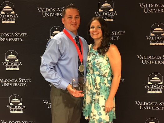 Staff Sgt. Joshua Dunn, 23d Component Maintenance Squadron aerospace propulsion craftsman, poses with his wife, Brentnie, as he holds the Military Hero Award during the American Red Cross of South Georgia Hero Awards, March 27, 2017, in Valdosta, Ga. On Feb. 3, Dunn utilized his Self-Aid & Buddy Care military training to ensure safety at the scene of a car accident scene. by blocking oncoming traffic and assessing the victim's ailments until paramedics arrived. (Courtesy photo)