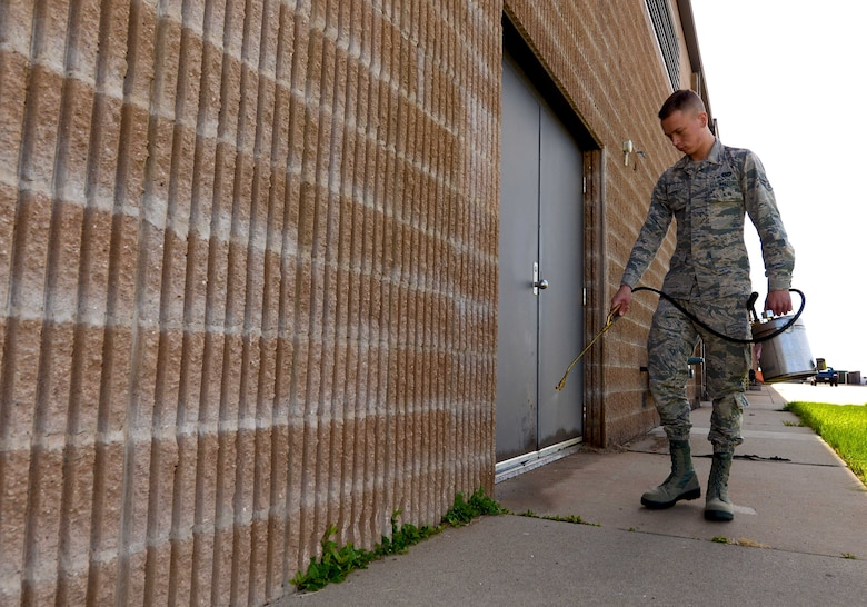Airman 1st Class David Pitts, a pest management apprentice assigned to the 28th Civil Engineer Squadron, sprays pesticide along the backside of the 28th Maintenance Squadron at Ellsworth Air Force Base, S.D., April 7, 2017. Pest management utilize tools such as mouse traps, live traps, bird, and various sprayers to prevent pests from nesting on base. (U.S. Air Force photo by Airman 1st Class Donald C. Knechtel)