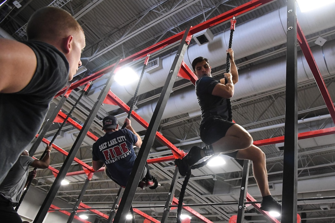 Juan Mendez performs climbs a rope during the 'FitCon Frontline Throwdown' at the Salt Palace in Salt Lake City, Utah, April 21. The four-person team took turns climbing the rope for 10 minutes. (R. Nial Bradshaw/U.S. Air Force)