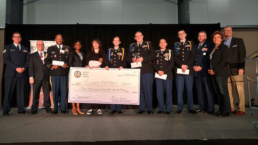 Five students from Alamo Heights Army JROTC pose on stage with their mentors as well as civic and cyber industry officials as they accept awarded scholarship money from the Armed Forces Communications and Electronics Association (AFCEA) during the Mayor's Cyber Cup luncheon April 6, 2017 in San Antonio, Texas. The cadets were one of the five Alamo Heights cyber teams that competed in the CyberPatriot Cyber Defense Competition, placing fourth overall in their division. Staff Sgt. William Jones (far left), 92nd Cyberspace Operations Center, led the team of Airmen that mentored the students. (Courtesy photo)
