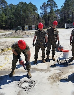 On March 20, 2017, Marines attached to Combat Engineer Officer course 3-17 (CEO 3-17) use a hammer drill to conduct spall repairs.  During their period of instruction, CEO students learn to conduct spall repairs, crater repairs, and lay AM2 matting in order to plan for airfield damage repair projects.  Pictured from left to right:  Second Lieutenants Joshua Raphaelson, Alexander Irwin, and Dylan Chung.