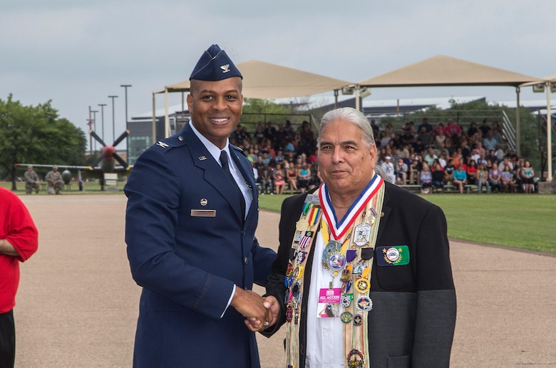 Col. Roy Collins, 37th Training Wing commander, give San Antonio Fiesta Commission president Erwin De Luna a gift during the Air Force Basic Military Training Fiesta graduation Parade April 21, 2017, at Joint Base San Antonio-Lackland, Texas. Each year, members of the Fiesta Royalty Court conduct the Royal Review of a BMT graduation during Fiesta San Antonio, a 10-day celebration of military history to honor the life and memory of the members who died in the Battle of the Alamo and the Battle of San Jacinto. Servicemembers from around JBSA participate in Fiesta San Antonio activities representing the progression of the United States military. (U.S. Air Force photo by Johnny Saldivar)
