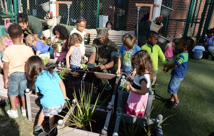 Col. James C. Carroll III (center), commanding officer, Marine Corps Logistics Base Albany, joins students and personnel at the installation's Child Development Center for the 2017 Earth Day observance, here, April 21. The annual event teaches young scholars the importance of preserving the environment through planting and caring for flowers as well as fruit-bearing bushes around the perimeter of the children's playground.
