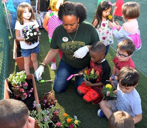 Students and personnel at the Child Development Center, aboard Marine Corps Logistics Base Albany, plant flowers as well fruit-bearing bushes in observance of the 2017 Earth Day, here, April 21. The annual event teaches young scholars about the importance of preserving the environment through planting and caring for the foliage, which they have planted in containers situated around the perimeter of the children's playground.