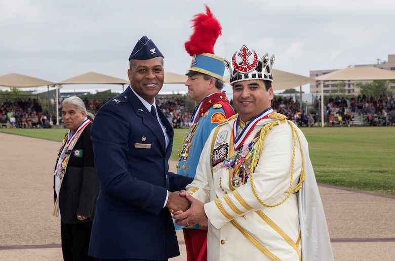 Col. Roy Collins, 37th Training Wing commander, presents a gift to 2017 Fiesta Royalty, Fernando Reyes of the Rey Feo Consejo Educational Foundation, April 21, 2017, at Joint Base San Antonio-Lackland, Texas. The full-scale Basic Military Training Graduation Parade is the only military graduation incorporated into Fiesta San Antonio, the city's 10-day celebration to honor the memory of the heroes of the Alamo and the Battle of San Jacinto. Over the past century, Fiesta has grown into a celebration of San Antonio's rich and diverse cultures. Military representatives from throughout San Antonio participate in receptions, parades, pilgrimages and memorials. (U.S. Air Force photo by Johnny Saldivar)
