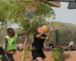 Army Pfc. Darian Hampton of Task Force Toccoa sneaks past a Cameroonian defender for a layup during a basketball game with American and Cameroonian service members in Garoua, Cameroon, April 21, 2017. The task force, which is supporting Cameroon's efforts against Boko Haram, decided to hold the game to help build better cohesion between American and Cameroonian military members. DoD photo by Sean Kimmons