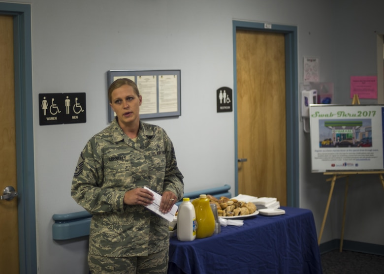 """Master Sgt. Crystal Connelly, the 49th Medical Group Diagnostic and Therapeutics flight chief, addresses a room of people during the MDG's Swab-Thru event, at Holloman Air Force Base, N.M. on April 20, 2017. The Swab-Thru, coordinated with the """"Salute to Life"""" program, is a special drive-thru bone marrow registration event. Connelly was inspired to bring the program to Holloman after her mother-in-law was diagnosed with cancer. (U.S. Air Force photo by Airman 1st Class Alexis P. Docherty)"""