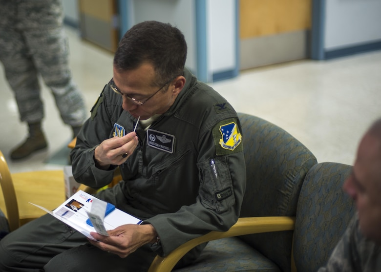 """Col. Houston Cantwell, the 49th Wing commander, swabs the inside of his cheek while registering for the """"Salute to Life"""" program during the 49th Medical Group's Swab-Thru event, at Holloman Air Force Base, N.M. on April 20, 2017. The Swab-Thru, coordinated with the """"Salute to Life"""" program, is a special drive-thru bone marrow registration event. Members who are interested in registering can stop by the Medical Group lab during duty hours. The MDG will continue to host registration drives throughout the year, but would like for other groups, squadrons and flights to get involved and host events. (U.S. Air Force photo by Airman 1st Class Alexis P. Docherty)"""