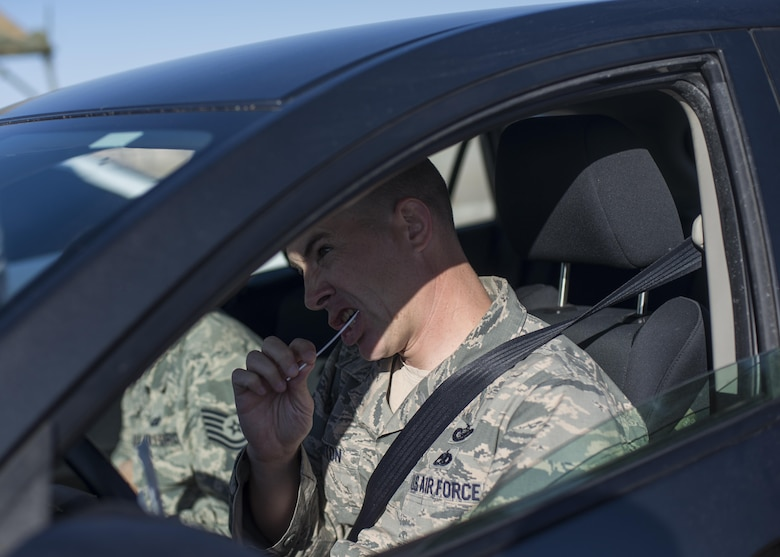 """Tech. Sgt. Jeffry Howerton, Holloman Air Force Base broadcast communication non-commissioned officer in charge, swabs his inner cheek during the 49th Medical Group's Swab-Thru event, at Holloman Air Force Base, N.M. on April 20, 2017. The Swab-Thru, coordinated with the """"Salute to Life"""" program, is a special drive-thru bone marrow registration event. The event was held in the parking lot across from the MDG. Over 100 Airmen nestled their cars into the lot and registered with the """"Salute to Life"""" program to show their support for victims of cancer. (U.S. Air Force photo by Airman 1st Class Alexis P. Docherty)"""