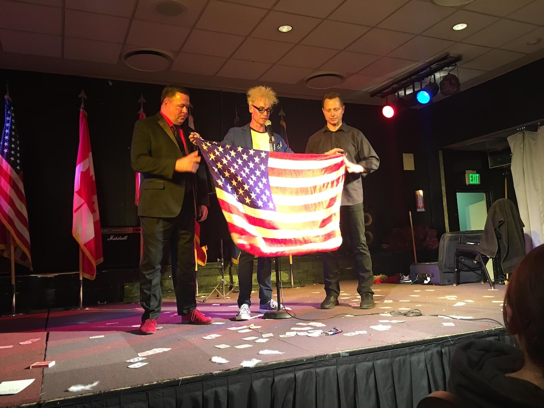(Left) Maj. Wayne Capps, 315th AW Public Affairs Officer, along with Murray Sawchuck (Center), and Dace Chandler perform magic illusions April 16, 2017, to military members in Greenland. The magicians made an American flag appear during an illusion to show appreciation to military service members and families. (Courtesy photo)