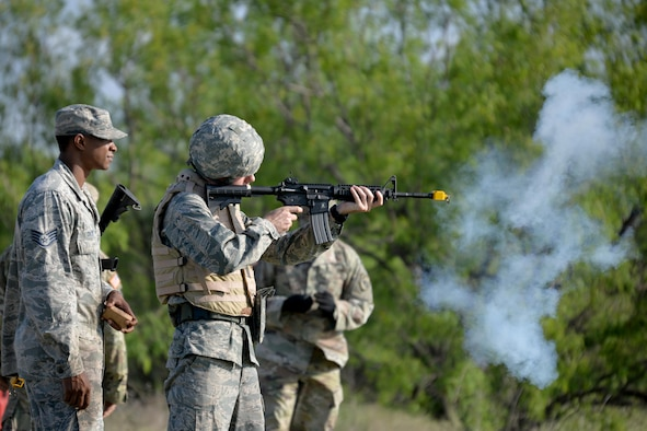 U.S. Air Force Staff Sgt. Philips Dixion, field training exercise instructor, teaches a cadet how to properly hold and aim a M4 Carbine during a field training exercise at Camp Sentinel on Goodfellow Air Force Base, Texas, April 21, 2017. The cadets and their adversaries used blanks to simulate a combat enviroment. (U.S. Air Force photo by Airman 1st Class Randall Moose/Released)