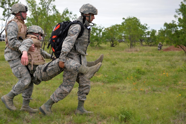 "Two Angelo State University Air Force ROTC Detachment 847 Cadets carry a ""wounded"" Airman after encountering an Improvised Explosve Device during a field training exercise at Camp Sentinel on Goodfellow Air Force Base, Texas, April 22, 2017. During the first half of day-one, the cadets learned a variety of skills to include Self-Aid and Buddy Care, weapon familiarization and leading group movements, which were tested in mock combat conditions. (U.S. Air Force photo by Airman 1st Class Randall Moose/Released)"