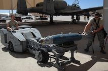 U.S. Air Force Airman 1st Class Zachary Rhodes and Staff. Sgt. Christopher Ouellet, 357th Aircraft Maintenance Unit load crew team members, prepare to load a Guided Bomb Unit-38 onto an A-10C Thunderbolt II during a load crew of the quarter competition at Davis-Monthan Air Force Base, Ariz., April 21, 2017. The load crews were required to complete their assigned tasks in accordance with their technical orders in the least amount of time possible. (U.S. Air Force photo by Airman 1st Class Frankie D. Moore)