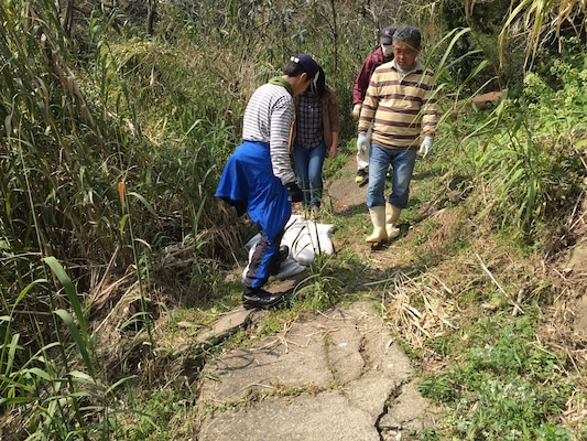 Volunteers work on trail maintenance in the Tawaraga-Uro Cho community as part of a local cleanup effort.