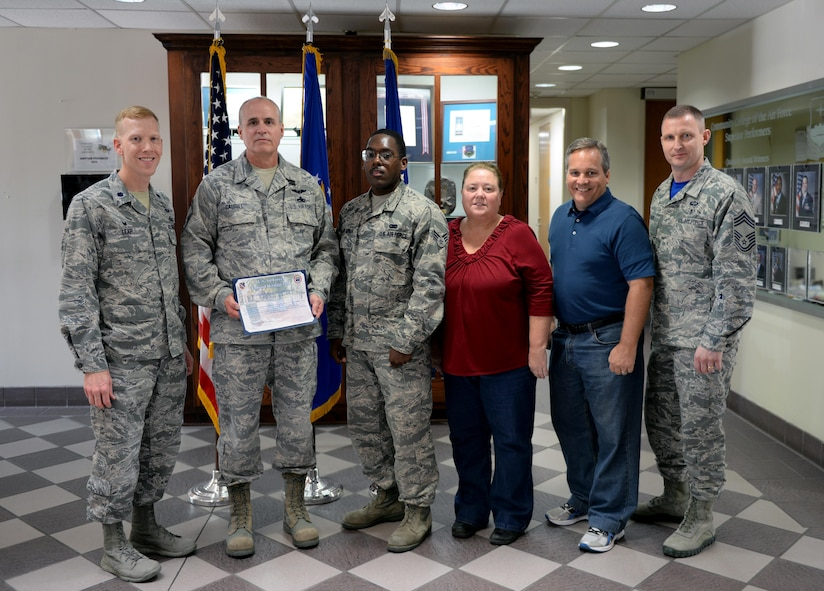Members of the Community College of the Air Force stand with the 500,000th CCAF graduate on Maxwell Air Force Base, Ala., April 21, 2017. Senior Master Sgt. Duane Caudill graduated as the 500,000th graduate in November 2016, marking a historical event for the CCAF since opening its doors in 1972. (U.S. Air Force photo/Senior Airman Tammie Ramsouer)